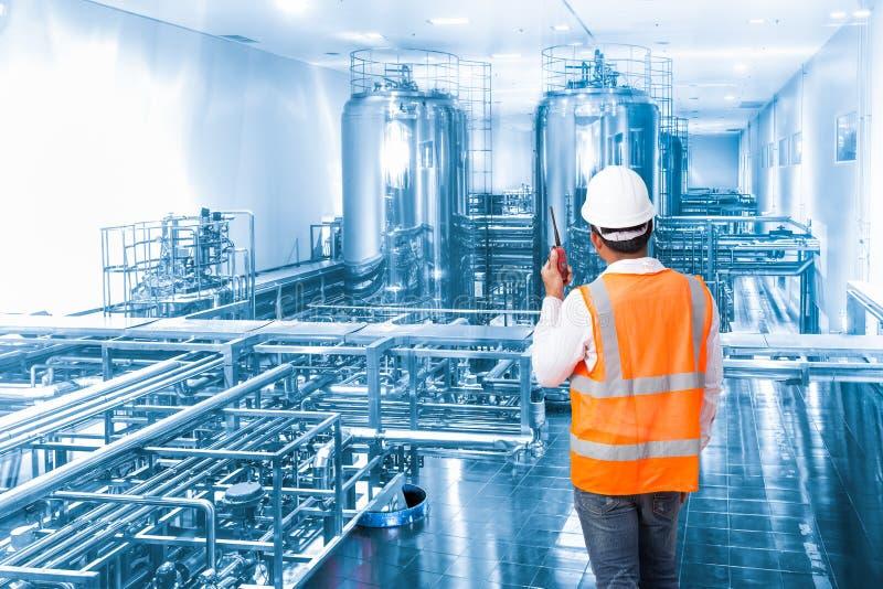 Przemysłowy inżynier pracuje w fabryce z opowiadać na radiu fotografia royalty free