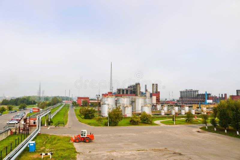 Przemysłowy krajobraz z fabrykami chemikaliów, drymbami i kolumnami, Below jest pomarańczowy ciągnik Dymu komes od reaktoru obraz stock