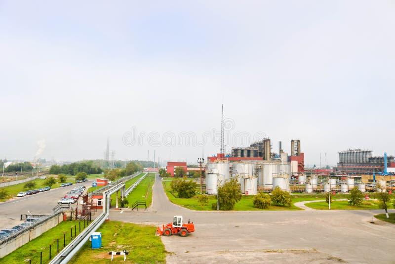 Przemysłowy krajobraz z fabrykami chemikaliów, drymbami i kolumnami, Below jest pomarańczowy ciągnik Dymu komes od reaktoru obrazy stock