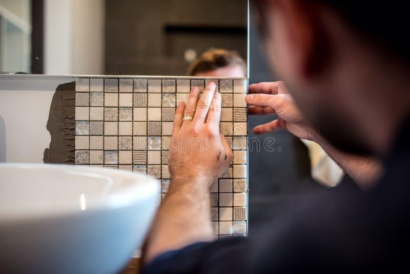 Przemysłowy mężczyzna pracownik stosuje mozaik płytki w łazienek ścianach zdjęcia stock