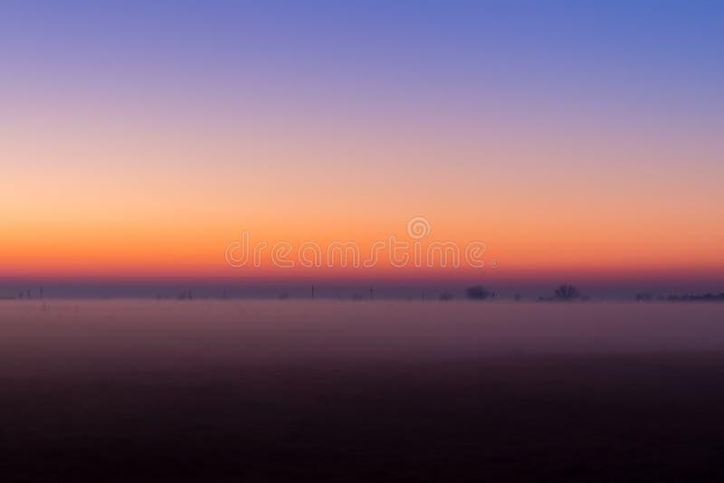 Przemysłowy mgłowy krajobraz, sylwetka stara fabryka przeciw zmierzchu niebu i mgła przy błękitną godziną przy nocą, obraz royalty free