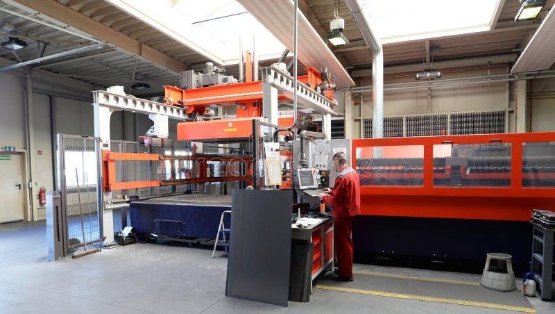 Przemysłowy pracownik działa laserową tnącą maszynę - pracownik w metalworking firmie obraz royalty free