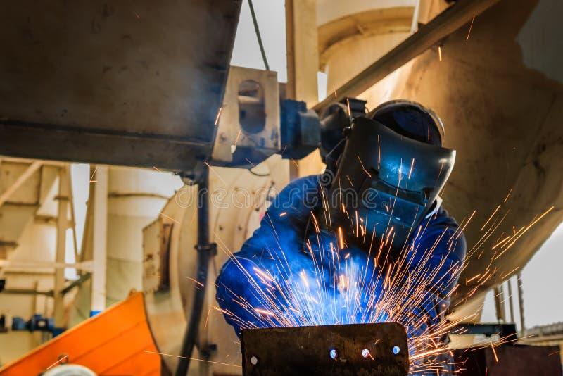 Przemysłowy pracownik jest spawalniczym metalem w fabryce fotografia royalty free