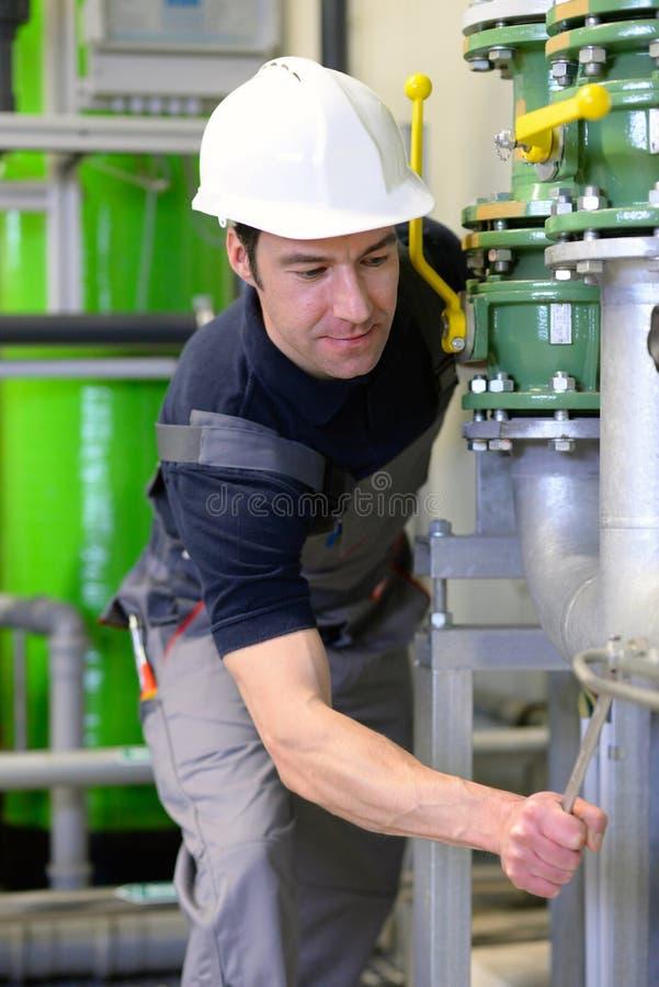 Przemysłowy pracownik naprawia maszyny i wyposażenie w rafinerii zdjęcie royalty free