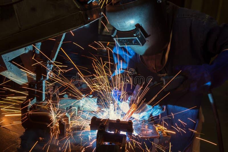 Przemysłowy pracownik spawa remontową metal część w samochodowej fabryce obraz royalty free