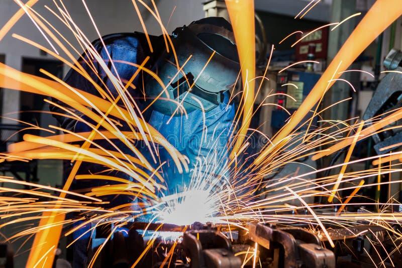 Przemysłowy pracownik spawa remontową metal część w samochodowej fabryce fotografia royalty free