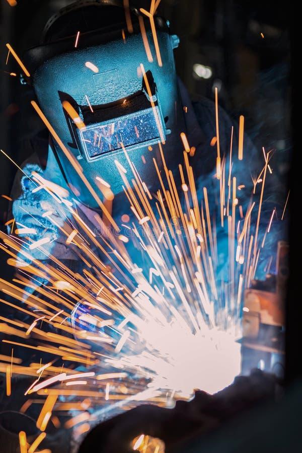 Przemysłowy pracownik spawa wcielający samochodową część w fabryce zdjęcie royalty free