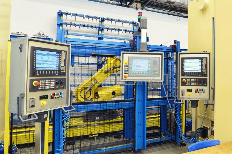 Przemysłowy robot z kontrolną jednostką w fabryce dla machinalnego e fotografia stock