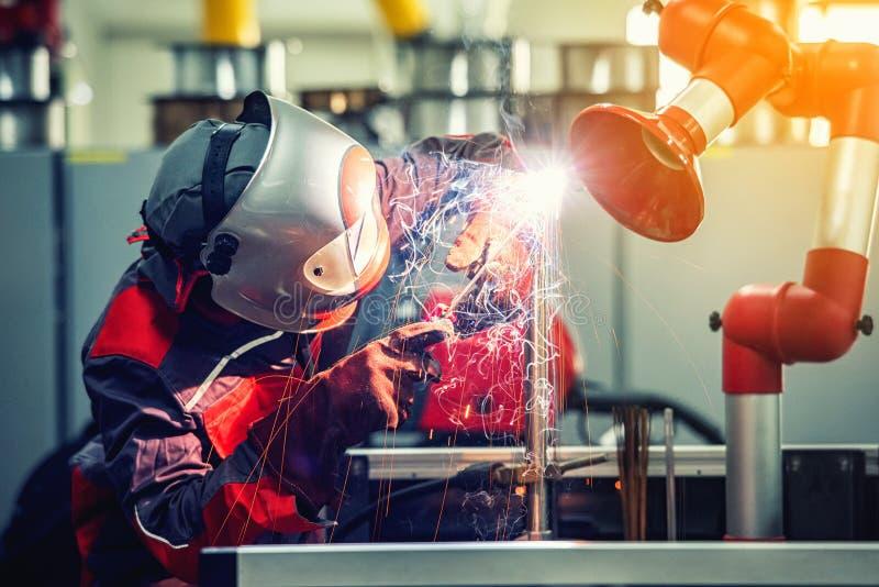 Przemysłowy spawacza pracownik jest spawalniczym metalu częścią w fabryce obraz stock