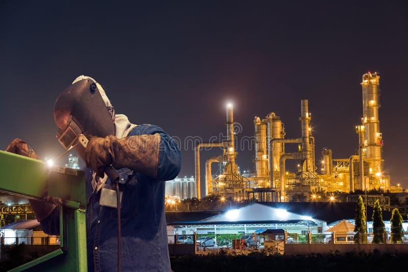 Przemysłowy spawalniczy pracownik przy zakładem petrochemicznym zdjęcia stock
