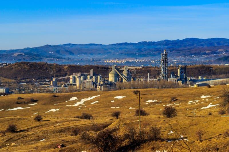 Przemysłowy teren wewnątrz w tle z dymienie fabrycznymi kominami, lasem i górami, zdjęcia stock