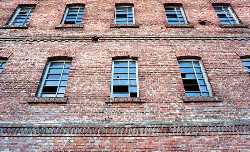 Przemysłowy zaniechany budynek rujnuje fasady ścianę, robić czerwona cegła, okno z łamanym szkłem obraz stock