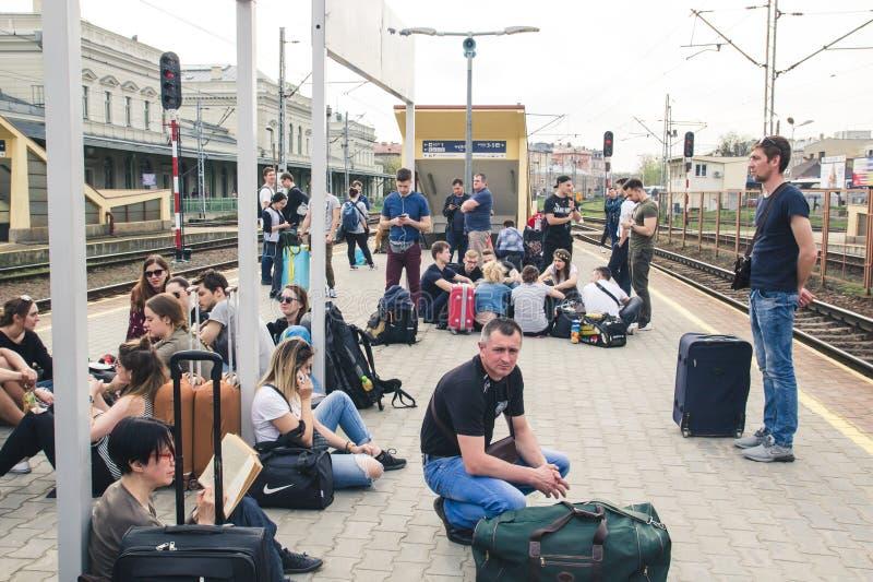 PRZEMYSL, POLONIA, el 15 de abril de 2018, mucha gente con equipaje en la plataforma que espera el tren retrasado imagen de archivo