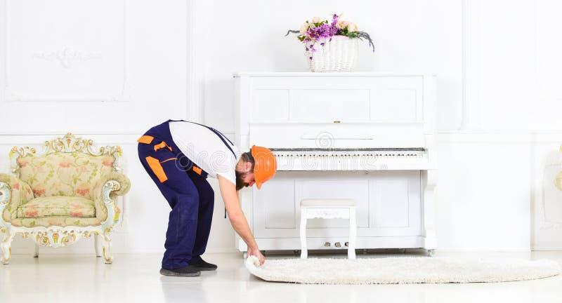 Przenosić pojęcie Ładowaczów wrappes dywanowi w rolkę Mężczyzna z brodą, pracownik w kombinezonach i hełma toczny dywan, biały zdjęcia stock