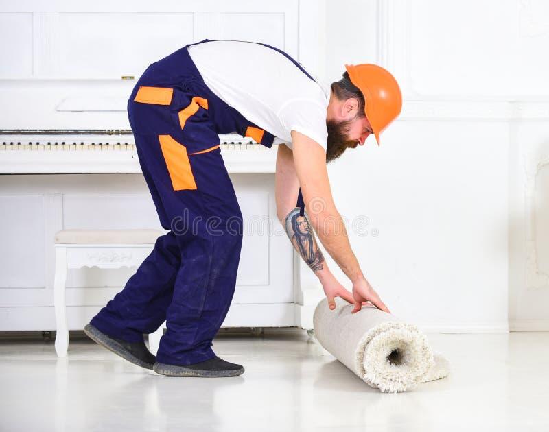 Przenosić pojęcie Mężczyzna z brodą, pracownik w kombinezonach i hełma toczny dywan, biały tło Ładowaczów wrappes obraz stock