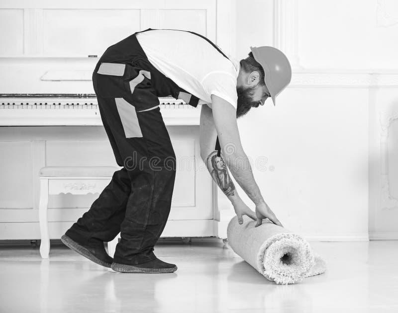Przenosić pojęcie Mężczyzna z brodą, pracownik w kombinezonach i hełma toczny dywan, biały tło Ładowaczów wrappes zdjęcia stock