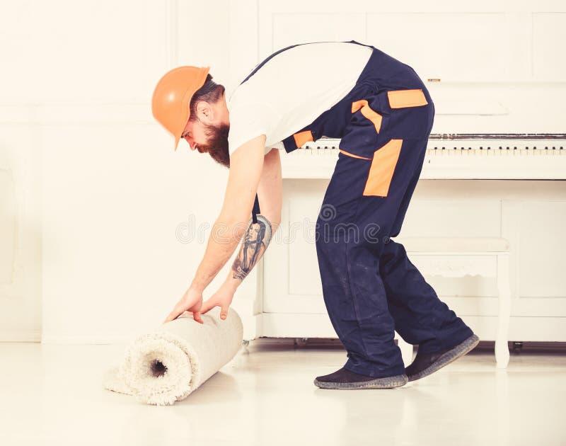 Przenosić pojęcie Mężczyzna z brodą, pracownik w kombinezonach i hełma toczny dywan, biały tło Ładowaczów wrappes fotografia stock