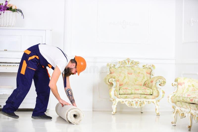 Przenosić pojęcie Mężczyzna z brodą, pracownik w kombinezonach i hełma toczny dywan, biały tło Kurier dostarcza zdjęcia royalty free