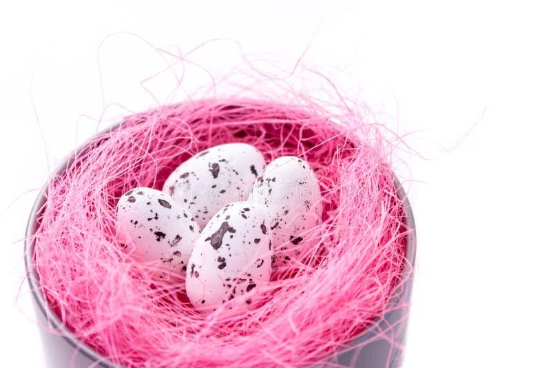 Przepiórek jajka w różowym sizalu gniazdeczku w metalu boksują na bielu, Easter karta obrazy royalty free