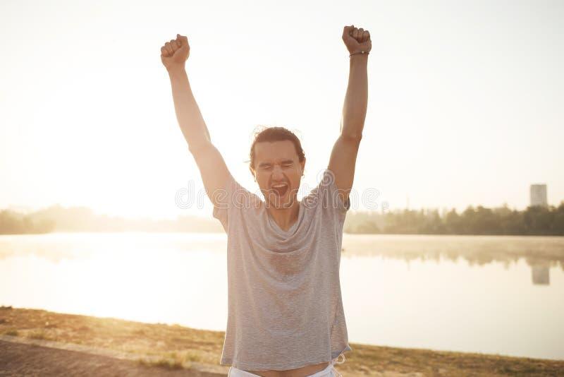 Przepocony mężczyzna z nastroszonymi rękami szczęśliwymi kończyć trening na wschodzie słońca obraz stock
