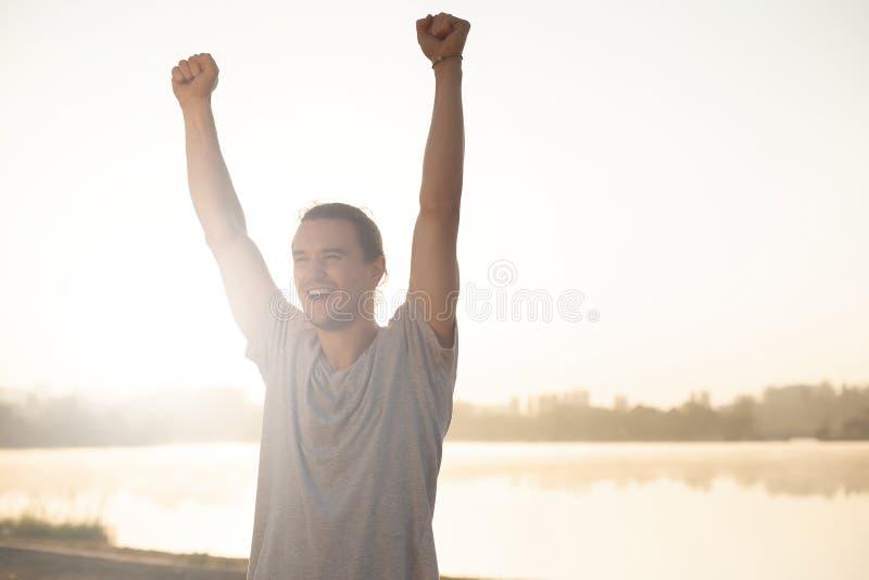 Przepocony mężczyzna z nastroszonymi rękami szczęśliwymi kończyć trening na wschodzie słońca zdjęcia royalty free