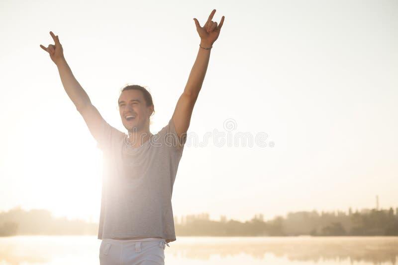 Przepocony mężczyzna z nastroszonymi rękami szczęśliwymi kończyć trening na wschodzie słońca obrazy stock