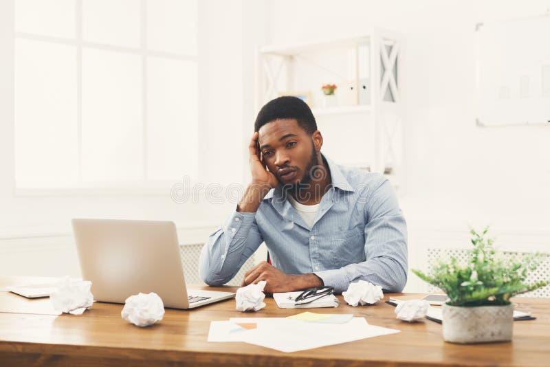 Przepracowywać się afroamerykańskiego pracownika przy miejscem pracy zdjęcie royalty free