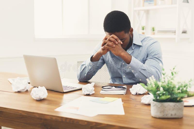 Przepracowywać się afroamerykańskiego pracownika przy miejscem pracy fotografia stock
