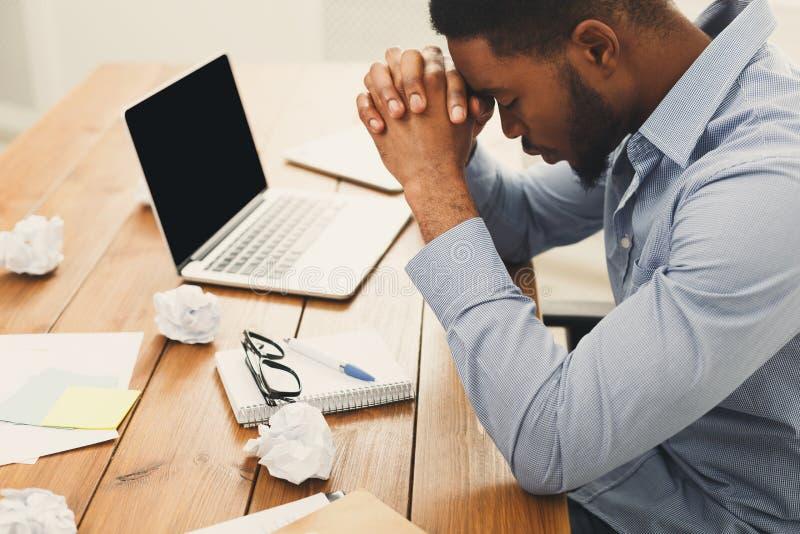 Przepracowywać się afroamerykańskiego pracownika przy miejscem pracy zdjęcie stock