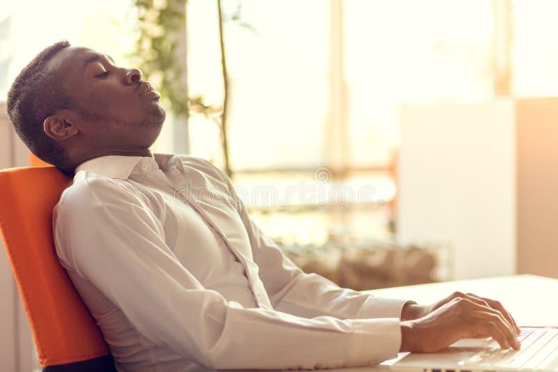 Przepracowywać się afroamerykańskiego pracownika w biurze Zmęczony i mieć migrenę podczas gdy pracujący na nowym projekcie obraz stock