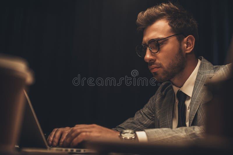 przepracowywać się młodego biznesmena pracuje z laptopem przy nocnym obraz royalty free
