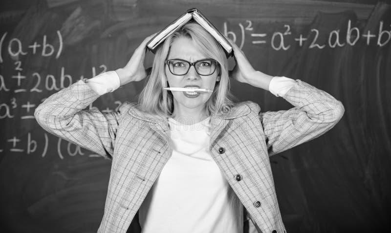 Przepracowywa się z zawodu i brak poparcie napędowy nauczyciel Nauczyciel kobieta z książkowym chalkboard tłem dlaczego zdjęcie royalty free