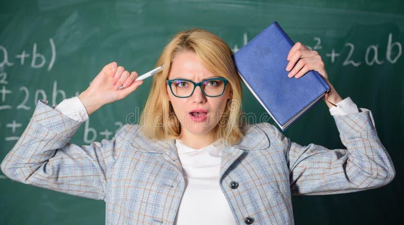 Przepracowywa się z zawodu i brak poparcie napędowy nauczyciel Nauczyciel kobieta z książkowym chalkboard tłem dlaczego zdjęcia stock