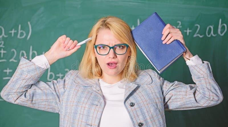Przepracowywa si? z zawodu i brak poparcie nap?dowy nauczyciel Nauczyciel kobieta z ksi??kowym chalkboard t?em dlaczego zdjęcie stock