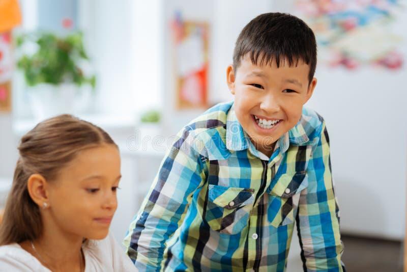przerwa Ładni śliczni dzieci ma małą przerwę w sala lekcyjnej podczas gdy siedzący zdjęcia stock