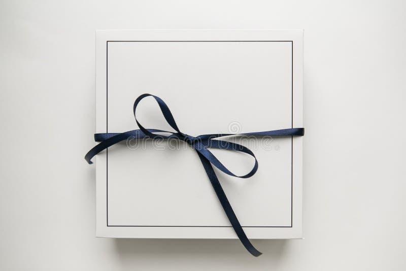 Przerzedże białego prezenta papierowego pudełko z błękitnego faborku łękiem, odosobnionym na białym tle obraz stock