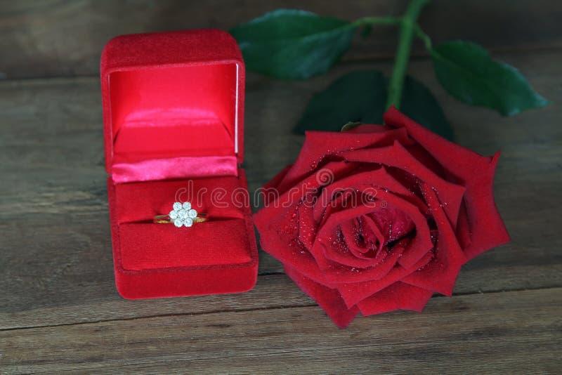Przerzedże czerwone róże i Diamentową obrączkę ślubną w czerwieni pudełku na drewnianym tle obrazy royalty free