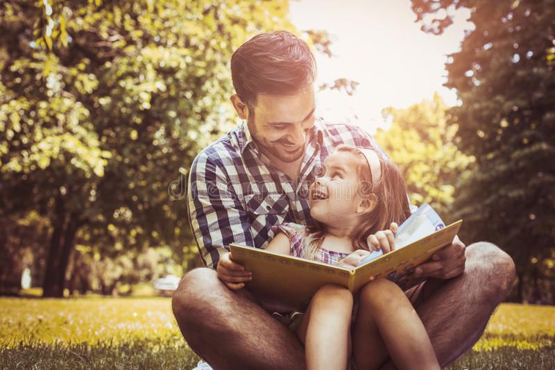 Przerzedże ojca obsiadanie na trawie z małą córką obraz royalty free