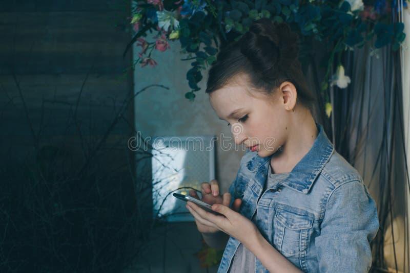 Przerzedże smutnego nastoletniego mienia telefonu komórkowego lamentujący obsiadanie na łóżku w jej sypialni z ciemnym światłem w zdjęcia stock