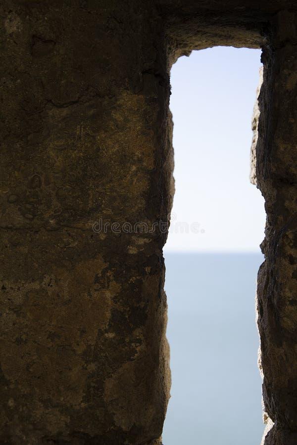 Przesmyk ochrony d?ugi pionowo okno forteca przegapia morze z horyzontem w plamie fotografia royalty free