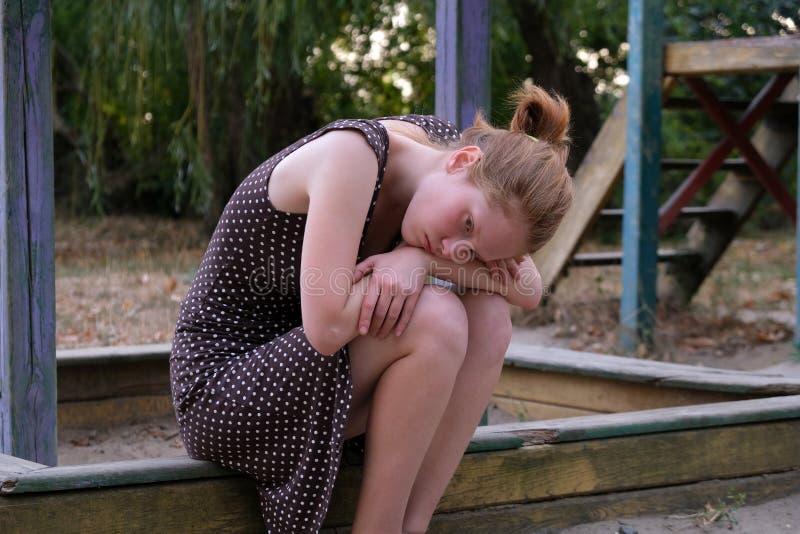 Przestępna dziewczyna siedząca na ławce na placu zabaw zdjęcie stock