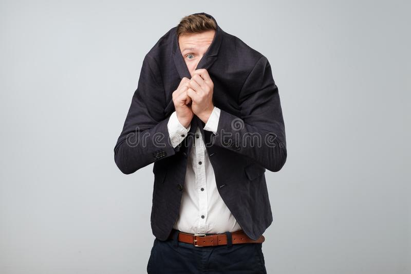 Przestraszony młody biznesowy mężczyzna chuje jego twarz od ryzykownego biznesu w kostiumu fotografia stock