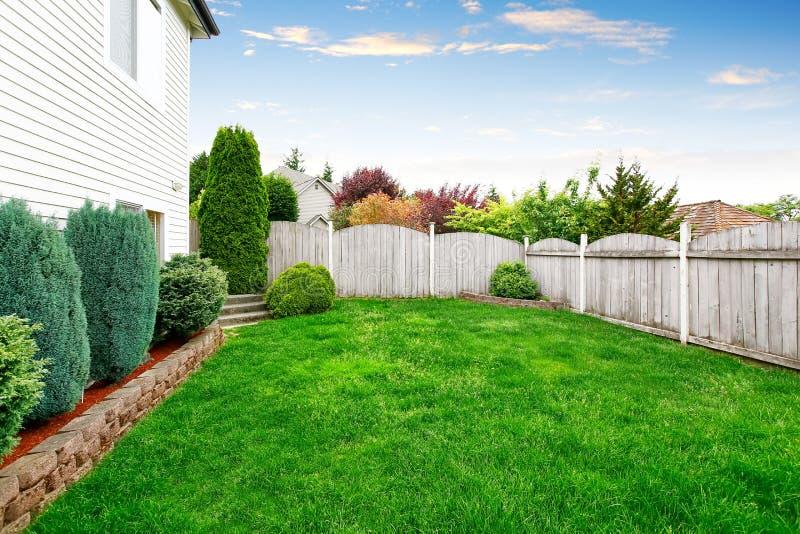 Przestronny podwórka teren z drewnianym ogrodzeniem i dobrze utrzymującym gazonem obrazy royalty free
