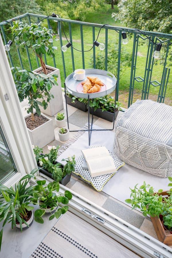 Przestrzeń dla posiłku i relaks na zielonym balkonie z comfy ottoman, sznurków światłami i tacą z słodkimi ciastami, i zdjęcie stock