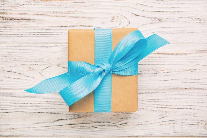 Przetwarzający papierowy prezenta pudełko z Błękitnym faborkiem na starym drewnianym białym tle Odgórnego widoku rocznik, tonując obrazy royalty free