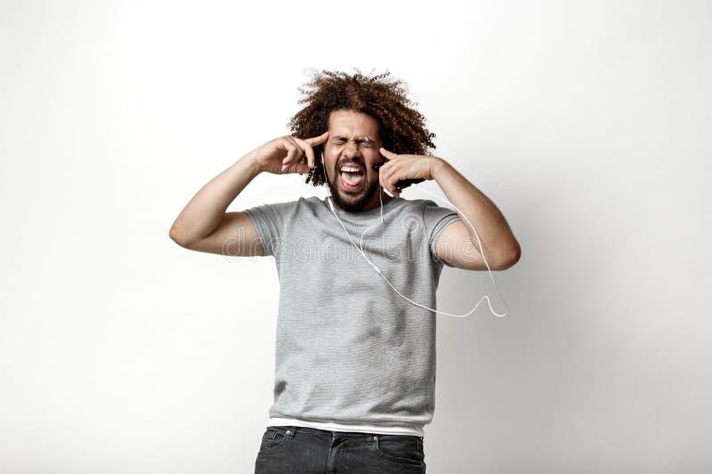 Przewodzący przystojny mężczyzna jest ubranym szarą koszulkę z latającym włosy słucha muzyka w słuchawkach obrazy royalty free