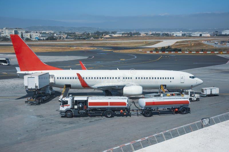 Przewozi samochodem z zbiornikiem, przyczepą lotnictwa paliwo podczas refueling przed lotem i zdjęcie stock
