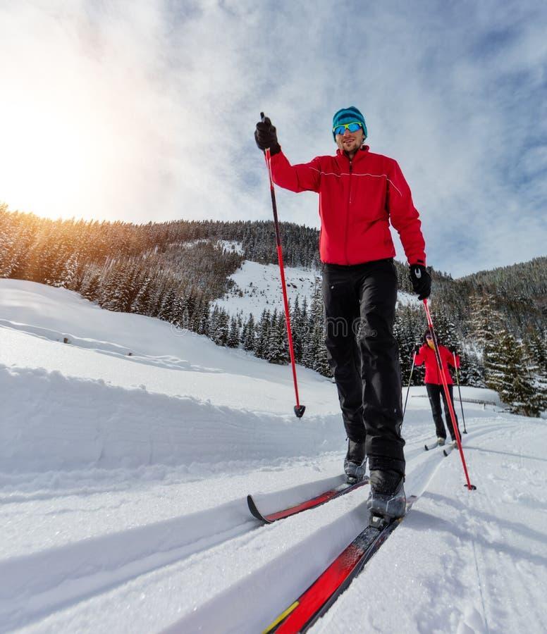 Przez cały kraj narciarstwo Młody człowiek i kobieta robi ćwiczeniu zdjęcia stock