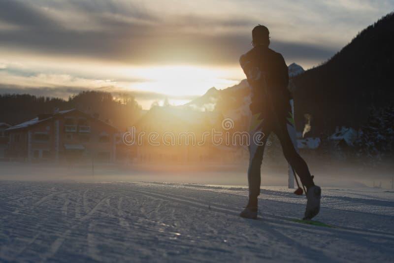Przez cały kraj narciarstwo przy zmierzchem w miejscowości turystycznej fotografia stock