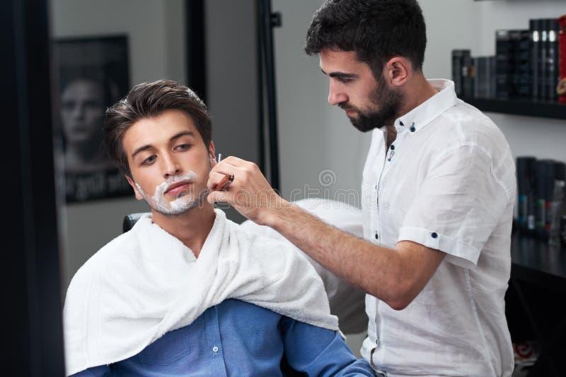 Przez lustra, fryzjer męski słuzyć klientów w salonie fotografia royalty free